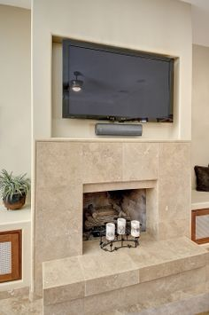 A sleek Travertine fireplace is ready to warm chilly winter evenings. Fireplace Tv Wall, Fireplace Surrounds, Fireplace Ideas, Stone Fireplaces, Classic Living Room, Travertine, Basement, New Homes, Flooring
