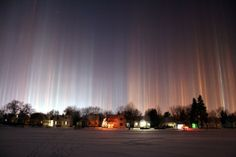 This phenomenon is known as 'light poles' and it can be seen at nights ower the large cities with different colored lights. They can only be seen during very cold weather (the temperature of -20 Celsius degrees or lower is required). Also the wind must not blow fast and there has to be a plenty of tiny ice crystals in the atmosphere.