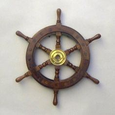 """12"""" Wood Ship Wheel - Pirate Shipwheel - Nautical Decor by ITDC. $33.25. By ITDC. Pirate Shipwheel. 12"""" Wood. Nautical Decor. This reproduction ship's wheel is an ideal size for almost any decor, at just fifteen inches in diameter. The brass is left unfinished, so that it may acquire an antique type finish over time. If that is not wanted, it may easily be polished away.  By ITDC"""