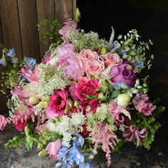 Whimsical pink bridal bouquet with blue accents and queen annes lace. Designed by Sullivan Owen.