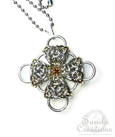"""Aurora's Cross is made with Bright Aluminum and accented with Jewelers Brass rings that connected together by four Aurora Chainmaille units. Our exclusive Chainmaille Weave, the """"Aurora"""", is only available through Saniki Creations. #chainmaille #pendant #necklace #handmadejewelry #sanikicreations"""