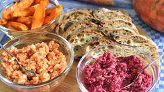 Drei Schälchen mit gebackenen Süßkartoffeln, Rote-Bete-Dip, Reiswaffel-Zwiebel-Dip und ein paar Scheiben Brot.