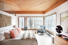 Cozy bedroom with neutral features, faux fur throw, sculptural art, wood carving, and blue chair in corner for reading