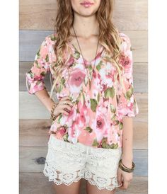 Floral Hi-Lo Top. 3/4 sleeves with wrap style front and a pink and white floral print. Wear it with crochet shorts. Buy it now at bohme.com