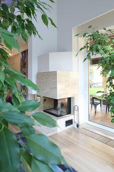 Kominek obłożony jest naturalnym marmurem, którego stonowana kolorystyka doskonale do równie naturalnej drewnianej podłogi. Fot. Bartosz Jarosz.