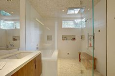 This bathroom has a large glass partition separating the bath and shower from the vanity.
