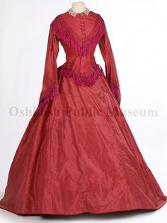 Large elliptical hoop wedding gown in a bright dark pink silk worn by Vesta Cornish for her 1871 wedding. Very full skirt with waist gathers in the back is plain; set-in large bell-shaped sleeves; fitted bodice falls in V to the front and to a tail in the back; yoke, bodice bottom and sleeves trimmed with three rows of tucks and silk dark pink fringe; front button closure with dark pink crochet buttons; attached white lace collar with attached rectangle-shaped stone brooch.