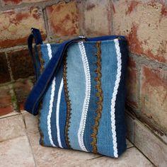 Džíska modrá prýmková Středně velká kabelka z tmavomodré recydžínoviny. Přední díl je ozdobený aplikací doplňkových odstínů džínoviny a prýmky v bílé a staromosazné barvě. Kabelka je pečlivě podlepená, dobře drží tvar, má modrou džínovou podšívku se třemi kapsami. Je uzavíratelná na pevný zip. Ucho zpevněné modrým popruhem je nastavitelné do 140 cm, ...