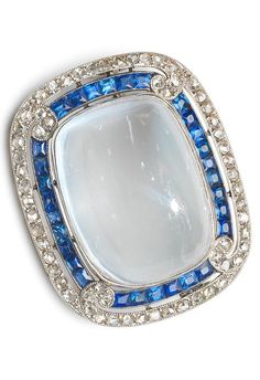 Cartier - A Belle Epoque moonstone, sapphire and diamond plaque brooch, circa 1915. The large cushion-shaped moonstone cabochon within a rectangular surround of French-cut sapphires and rose-cut diamonds, with a rose-cut diamond flourish at each corner, mounted in platinum, signed Cartier Paris, numbered, length 3.2cm. #Cartier #BelleEpoque