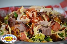 Santa Fe Salad.  Chopped romaine, black beans, corn, onion, tomato, cilantro, seasoned croutons and your choice of pork, brisket or chicken; drizzled with chipotle ranch and Sweet Baby Ray's and topped with shredded cheese.  Served with honey-kissed cornbread.