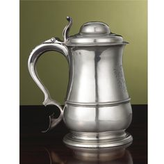 An Irish Silver Tankard, Thomas Walker, Dublin, circa 1750 of girdled baluster form, engraved with a contemporary crest above a vacant rococo cartouche, the domed cover crested and with openwork scroll thumbpiece, the double-scroll handle applied with rattail and terminating in a shield