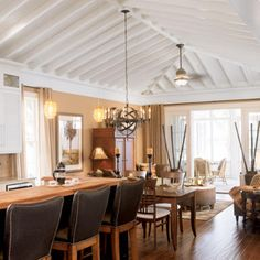 The designers created an informal dining area for family meals adjacent to the kitchen. The two rooms share a hipped roof, with an exposed bead board ceiling and rafters. This house has the most beautiful ceilings ever....