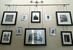 Gallery frames hanging by chain from a curtain rod with contrasting frames on wall.