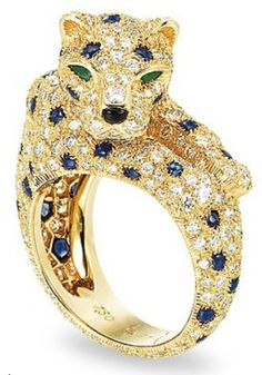A diamond, sapphire, and emerald panther ring by Cartier.  18k gold set with diamonds and sapphires to create the panther's spots.  Christie's description also says that the panther's head rotates, which is hard to imagine, but I'd love a chance to play with it. Via Diamonds in the Library.