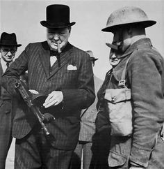 Winston Churchill with cigar and tommy gun- taken while he was visiting coastal defense positions near Hartlepool, July 1940