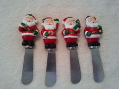 Santa Spreader Set of 4 by ? Each Santa dressed in traditional red suit/hat w/ white fur trim, had holly leaves/trim on hat, black boots and belt/buckle green mittens: 1) Santa carries brown toy bag over right shoulder; 2) Santa waving left hand hold candy cane in right hand; 3) holding Cmas tree on left shoulder; 4) holds something green? in left arm.