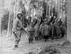 Soldier of the 12th Armored Division stands guard over a group of German prisoners April 1945.
