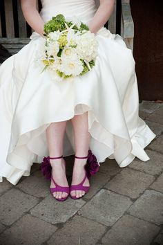 Bride in white dress with purple strap shoes with floral design sitting on bench holding a white, light green, and yellow bouquet -  photo by Portland wedding photographer Barbie Hull