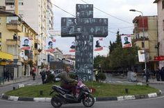 A cross in a street in the northern city of Shkoder, Albania, holds the pictures of 38 Catholic martyrs executed or tortured to death during the former communist regime Saturday, Nov. 5, 2016. Albanians celebrated their beatification after Pope Francis had officially recognized as martyrs Archbishop Vincens Prenushi and 37 other priests who died in prison or were murdered in 1945-1974 by the late communist dictator Enver Hoxha's regime. (AP Photo/Hektor Pustina)