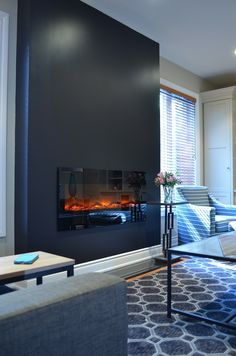This sleek black #fireplace wall with electric insert from Amantii replaced a bulky gas fireplace.