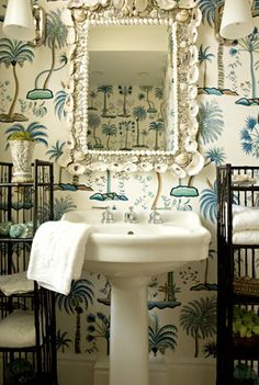 A British Plantation style powder room with blue and white palm print wallpaper; dark wood towel racks, and a shell-framed mirror.