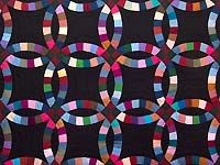 Almost Amish Double Wedding Ring Quilt from Amish Country Quilts  Love the solid colors and black background