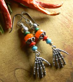Fun and colorful beaded Czech glass earrings with skeleton hand charms of pewter. A stacked arrangement of orange, red, green and blue Czech glass beads with accents of rustic pewter. The ear wires are hypoallergenic niobium in a gunmetal tone for a total length of 2.6 inches.