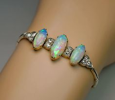 An Antique Edwardian Opal and Diamond Bracelet circa 1910 The silver topped gold bracelet is centered with three elongated oval opals which display a vibra