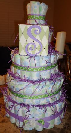 diy diaper cake w/ bow holder baby initial as centerpiece.