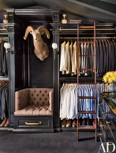 Now here's a seating arrangement in a men's closet you won't see very often. Bold - unique. I also love the use of the library ladder to add style and make it easy to get to the top shelf storage.