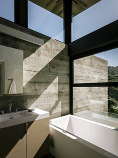 Modern eco-conscious pavilion in California by Feldman Architecture with passive solar energy in a bathroom clad with concrete walls.