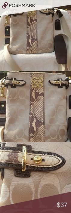 Coach Crossbody Bag C traditional with Fauk Snake Coach traditional C in light taupe, cream colored C's. Piped in chocolate brown/accents by the gold hardware, with the chocolate hang tag and strap that sits on your shoulder. Faux 🐍snake accents panel running down the front of the bag and by the hardware to hilite the richness of the accent colors. Long, strap is about 20 inches long, and no wear on it! There are 2 tiny marks on the gold hardware, unnoticeable when wearing, and one very…