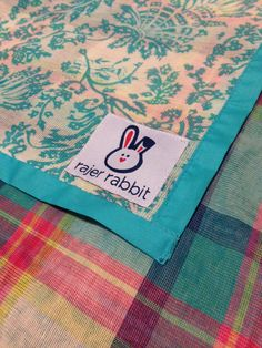 GOA MADRAS BLANKET 18.00 USD  24 x 24in  |  100% muslin cotton | double-sided design | handmade design with paisley printed front and madras plaid back with turquoise border | the perfect size for a security blanket  Colors available: Turquoise/Pink