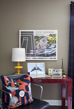 Fun boy's bedroom with warm gray walls paint color, glossy red West Elm Parsons Desk, blue curtains, comic book art and yellow lamp.