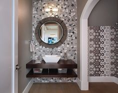 This powder room's grey color theme adds a pop of color to the white entrance hall. We especially love the stone background and floating vanity!
