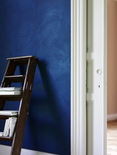 """Die Atmosphäre eines Raums lässt sich am besten mit Farbe verändern. Also, warum nicht mal eine Wand in tiefem Blau streichen? Schließlich soll Blau die Kreativität fördern und innovativ wirken.Wir empfehlen das wunderschöne, dunkle Blau aus Tim Mälzers Farbrezepten von Alpina, das es in den meisten Baumärkten gibt. """"Blaues Blut"""" heißt diese Nuance, die wir hier sehen - und die Wohnidee mit der angelehnten Leiter als Buchregal klauen wir auch gerne!"""