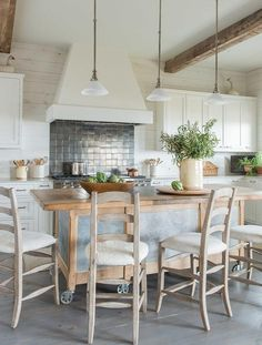 Rustic cottage kitchen features ladder back counter stools placed on gray wash wood floors in front of a freestanding rolling wood and steel island illuminated by three white frosted glass light pendants hung from a white ceiling accented with exposed wood beams.