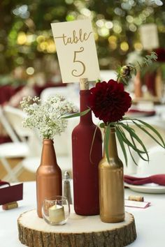 Gold and burgundy wine bottle centerpiece on wood round- decor idea from vineyard wedding from Gale Vineyards in California #winecountryweddings #VineyardWedding #winerywedding #galevineyards #weddingdecoration