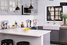The IKEA kitchen cabinetry is paired with simple white subway tile, stretching from counter to ceiling.