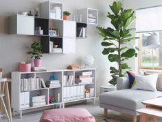 Un salón luminoso con una estantería abierta blanca y armarios de pared blancos y grises (unos con puertas y otros abiertos).