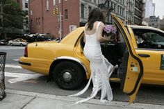 In a white dress getting into a yellow cab