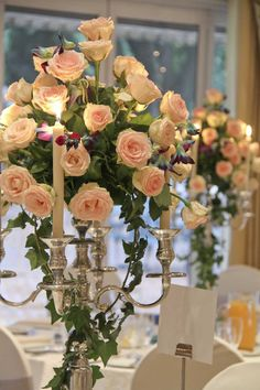 Wedding reception table flower arrangements. Candelabra with roses, blue dendrobium orchids and greenery.