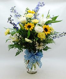 Blue Delphinium, White Lilies, Yellow Sunflowers, White Roses, Sunny White Daisies Accented with Gingham Blue and White Ribbon.