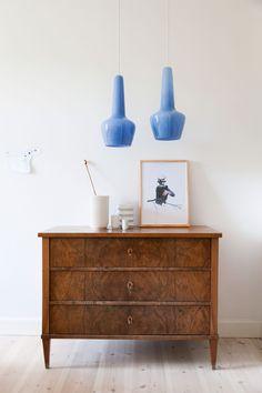 De blå Holmegaard-lamper og den mørke trækommode er et hot og smukt match. Kommoden i nøddetræ er et arvestykke fra Kristians familie. På kommoden står 'Lyngby'-vaser samt en vase af keramiker Bodil Manz.