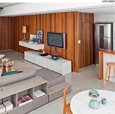 Painéis deslizantes ou pivotantes de madeira, como esses de peroba-rosa que fecham a cozinha embaixo e o quarto no mezanino, são ótimas soluções para integrar e isolar os ambientes em apartamentos. O projeto é do escritório Rocco, Vidal + Arquitetos.