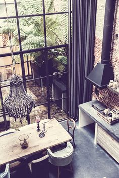 A loft home in Amsterdam -- brick wall, industrial stove hood, huge windows, weathered table, chandelier