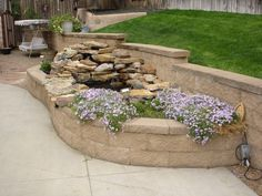 Block retaining wall, a raised planter bed and a waterfall built into the planter.
