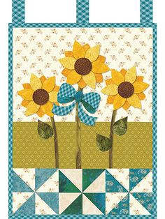 """This bright and happy wall hanging features a trio of cheerful sunflowers that are sure to make any room in your home shine with happiness! It includes full-size applique templates and detailed instructions. Finished size is 12 1/2"""" x 18"""". ..."""