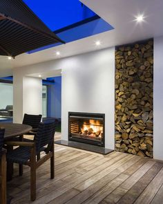 This outdoor fireplace has built-in wood storage right next to it.