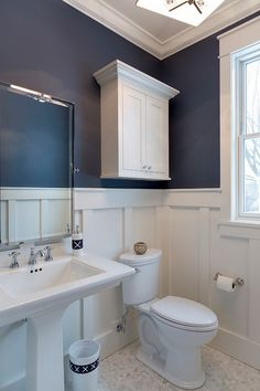 "Board and Batten Bathroom. What a great bathroom design! I love the combination of board and batten wainscoting with navy walls painted in Newburyport Blue by Benjamin Moore. The board and batten wainscoting was enameled in BM White Dove. The wainscoting was installed using multiple trim boards at approximately 54"" height. The floor tile is a marble hexagon."